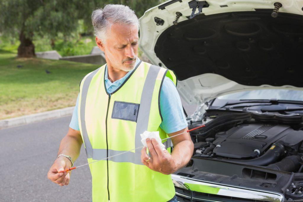 technician is fixing a broken car