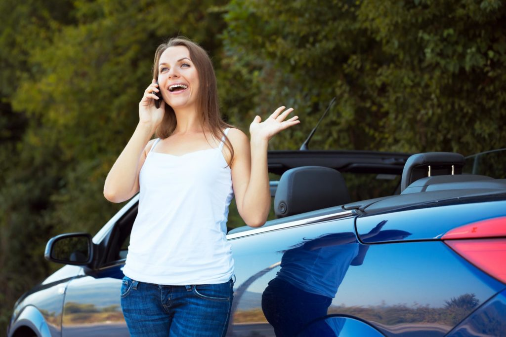 woman is talking on the phone next to her car